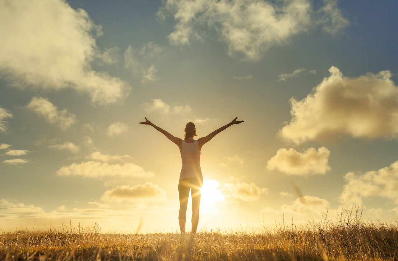Happy woman with arms in air feeling free
